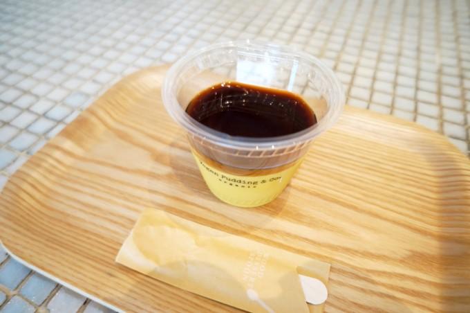 「TRIPLE  R」」の卵も牛乳も使用していない「ヴィーガンプリン」が白いタイルのテーブルの上の木のトレーにのっている写真