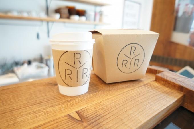 「TRIPLE R」のロゴ入りのテイクアウトドリンクやクラフト紙のランチボックスが木のカウンターの上に並んで置かれている写真
