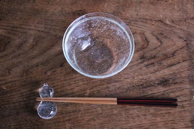 木のテーブルに置かれた伊藤亜木さんの気泡が入った硝子のひょうたん型箸置きと器