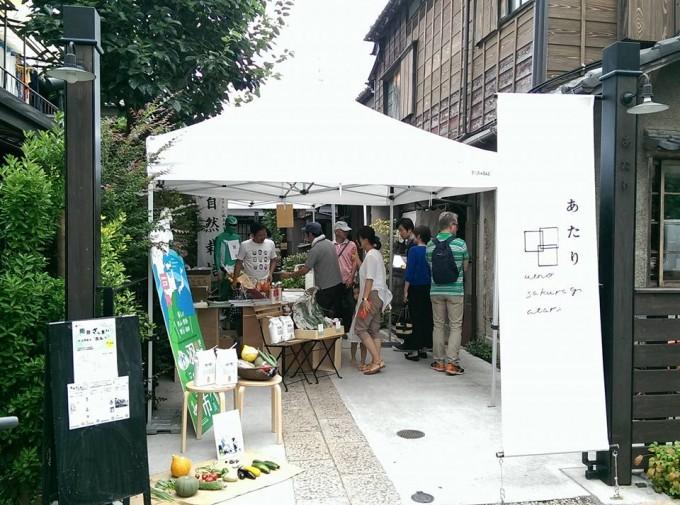 「上野桜木あたり」の「みんなのろじ」にお客さんが集まり、マルシェで物販を行っているところ