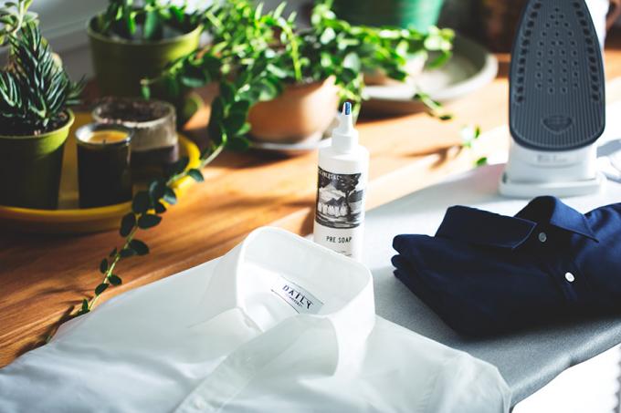 アイロン台の上に2枚のシャツとシミ落とし「PRE SOAP」が置かれている