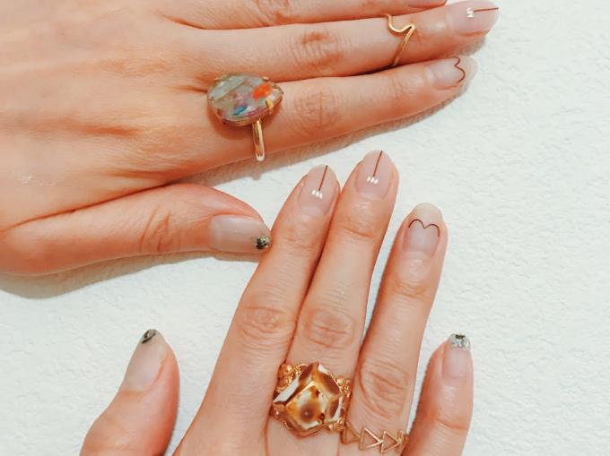 「nail atelier りぼん」のネイルにリングを合わせた手の様子