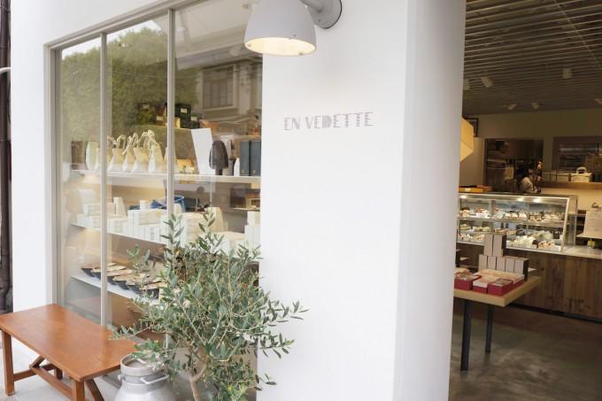 清澄白河のフランス菓子店「EN VEDETTE(アンヴデット)」の白い壁とロゴ、オリーブの木とベンチのある入り口付近の写真