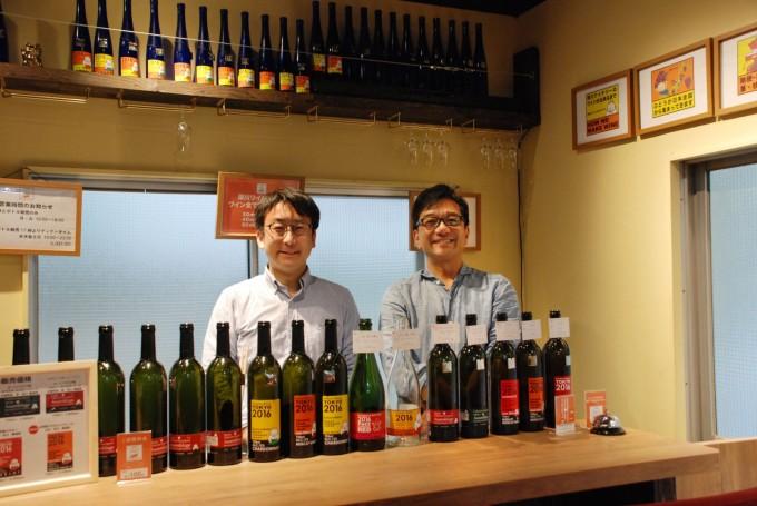 東京にある「深川ワイナリー」オーナーの中本徹さんと醸造責任者の上野浩輔さんが笑顔でカウンターの中に立っている写真