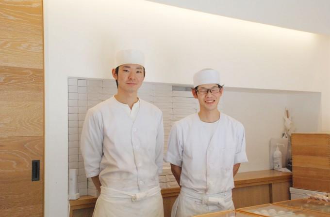 曳舟の大福とどら焼きの専門店「いちや」の店内に笑顔で立つ白い作業着を来た若い2人の和菓子職人