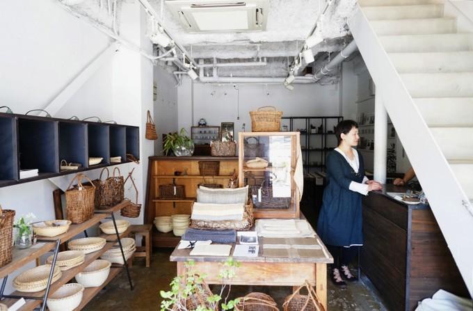 会津のかごなどが並ぶ「アムコ カルチャー&ジャーニー(amco culture&journey)」の打ちっ放し風の店内とワンピースを着たオーナーの女性