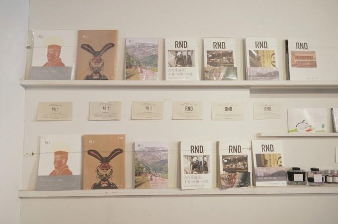 地方を取材して作った本「RND_輪土(りんど)」のバックナンバーが白い壁に作り付けの棚に並んでいる写真