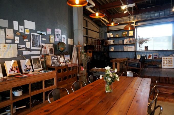 蔵前のカフェ「From afar 倉庫01」の店内の長い木のテーブルの客席や紙をたくさん貼った壁の見える店内の写真