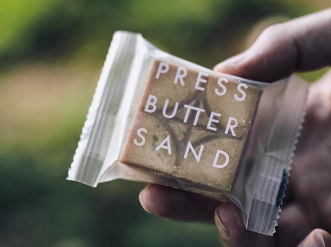 「PRESS BUTTER SAND(プレスバターサンド)」のバターサンドを手に持っているところ