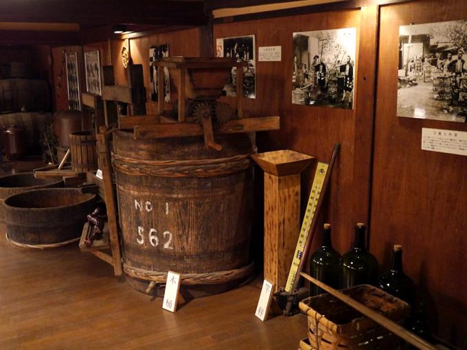 圧搾機や木樽、当時の白黒写真などが置かれた「くらむぼんワイン」の資料館