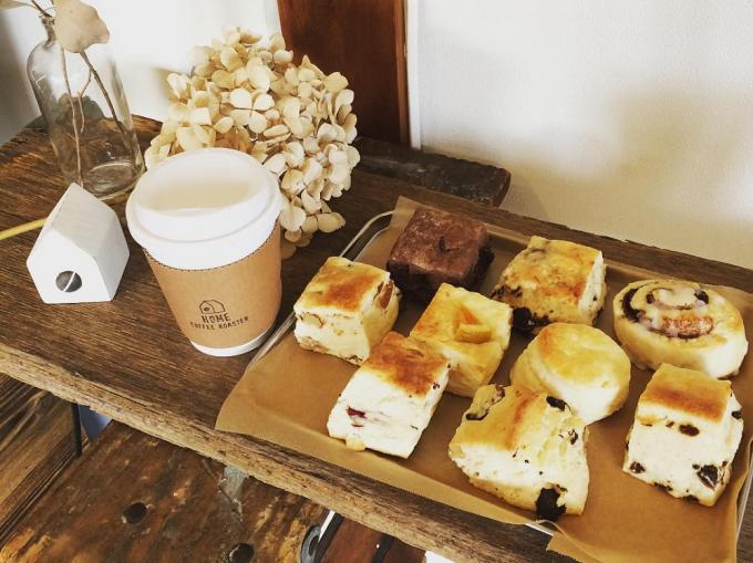 「HOME COFFEE ROASTER(ホームコーヒーロースター)」のコーヒーやスコーンなどが店内の木の棚に並んでいる