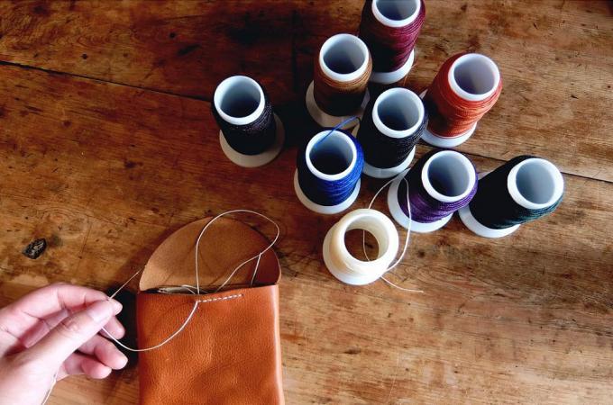 「9月製作」の革小物と色とりどりの糸