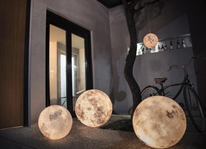 月型照明「Luna」が床に置かれたり、吊るされたりしている様子