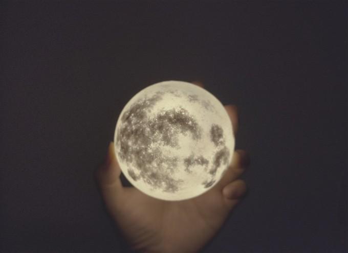 月型照明「Luna」を手に持っているところ