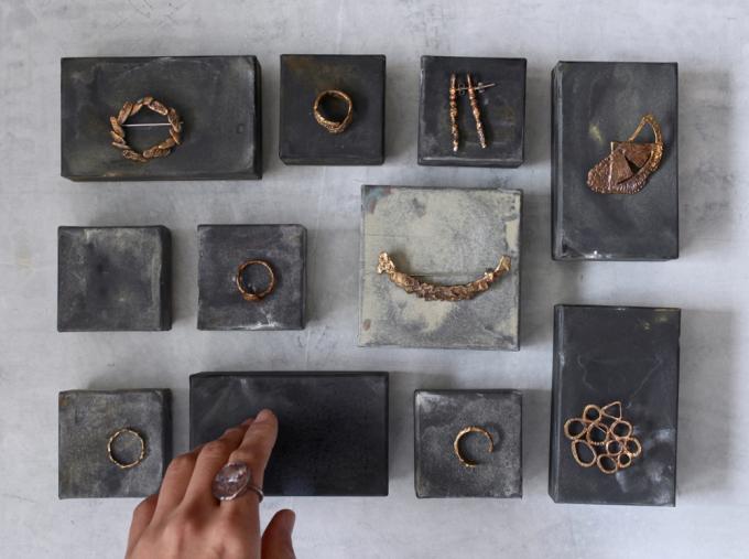 黒い箱の上に並べられた田中 友紀(たなかゆき)さんのゴールドのブローチやピアスなどのアクセサリー