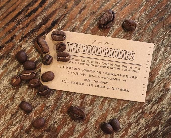 鎌倉のカフェ「THE GOOD GOODIES」のショップカードとコーヒー豆が木の机の上にのっている