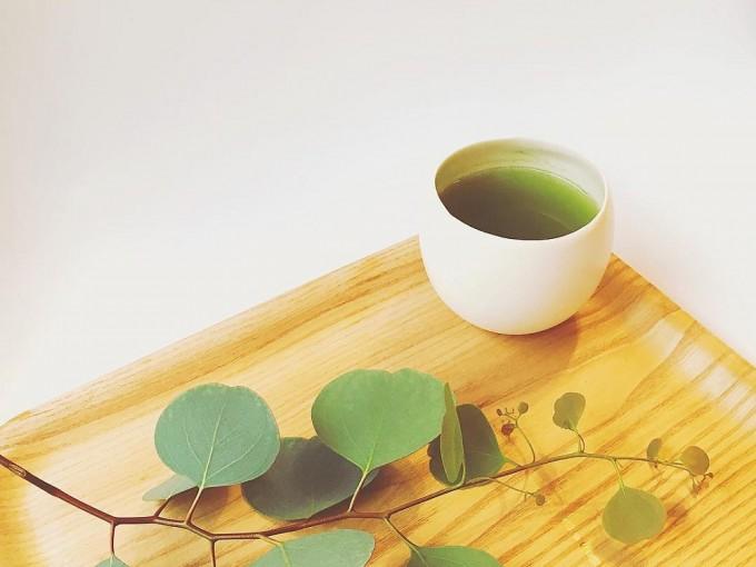 木のトレイの上に白い湯飲みに注がれた「茶屋 すずわ」のお茶と植物がのっている