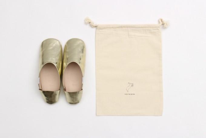 「PASS THE BATON(パスザバトン)」の金色のバブーシュと、収納用の巾着