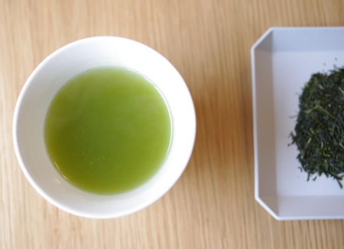 白い湯飲みに注がれた「茶屋 すずわ」の煎茶と、白くて四角い小皿に盛られた茶葉