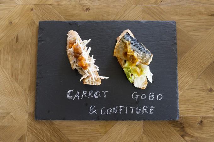 「佐渡保存」のゴボウと人参のコンフィチュールをパンに使って作った鯖やチーズなどのオープンサンドを黒い皿に盛り付けた写真