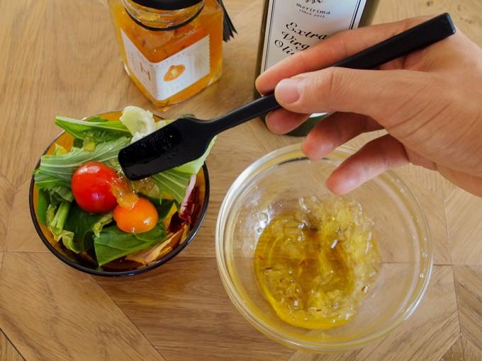 「佐渡保存」の野菜ジャムをガラスの器に入れてサラダにソースとしてかけている写真