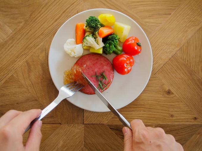 「佐渡保存」のジャムを白い皿に盛り付けた焼いたハムや野菜サラダにかけて食べようとしている写真