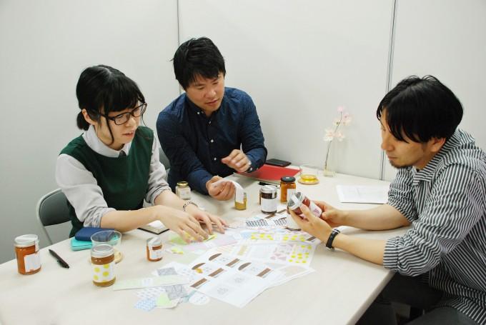 「佐渡保存」のジャムのパッケージデザインについて会議室で会議中の男性と女性