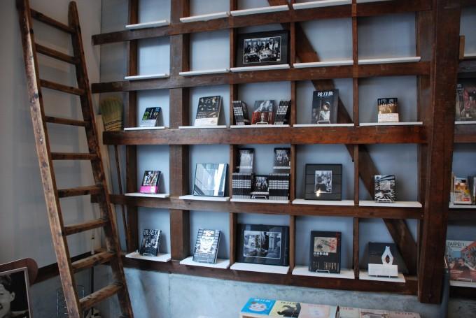 田原町の書店「Readin'Writin'」の木の棚に写真集が展示されているスペース