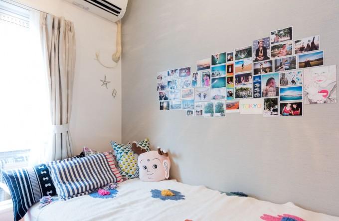 goodroomのリノベ賃貸「TOMOS」。ベッド横の壁には旅先で撮影した写真がずらり