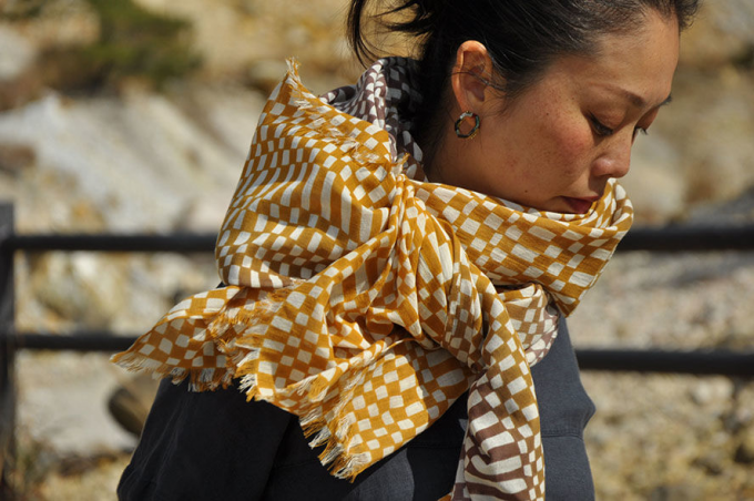 「よつめ染布舎」の『変わり市松』のストールを首に巻いた女性
