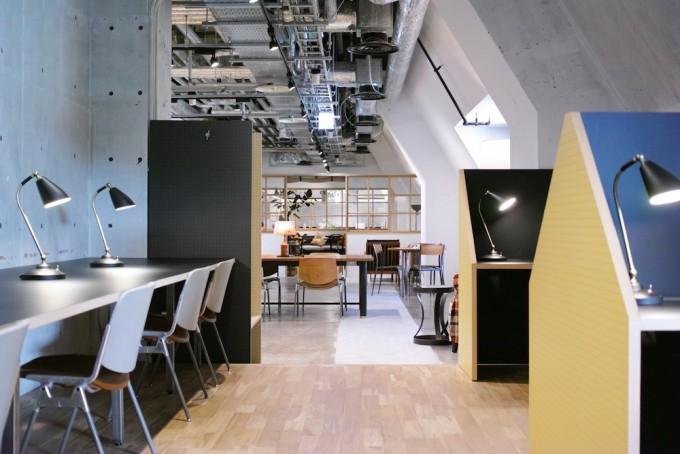 街のシェアスペース「BUKATSUDO」のテーブルや椅子が並べられたワークラウンジ