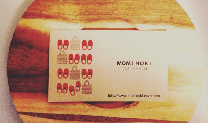 ウッドボードに乗った「北欧スマホケース屋 モミノキ」の名刺