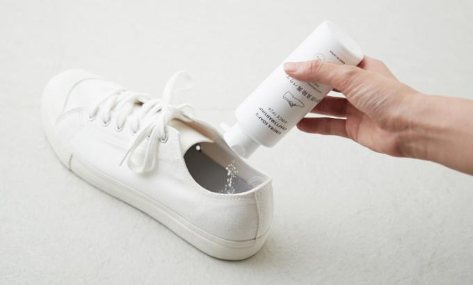 「木村石鹸」の除菌パウダーを靴にかけているところ