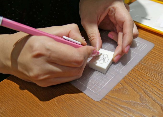 カッターナイフを使って手で消しゴムを削る作業中の写真