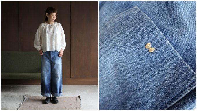 ワイドなデニムパンツを履いた女性/ポケットにある蝶の飾り