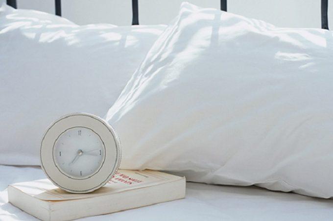 ベッドに置かれた枕と時計