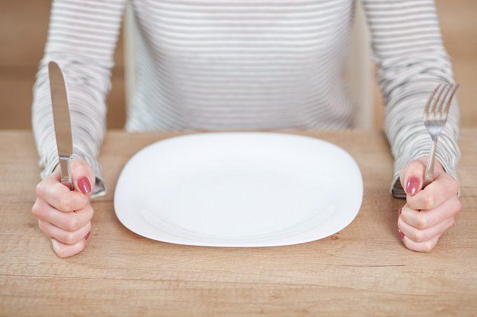 空のお皿の前でフォークとスプーンを握る女性の手元