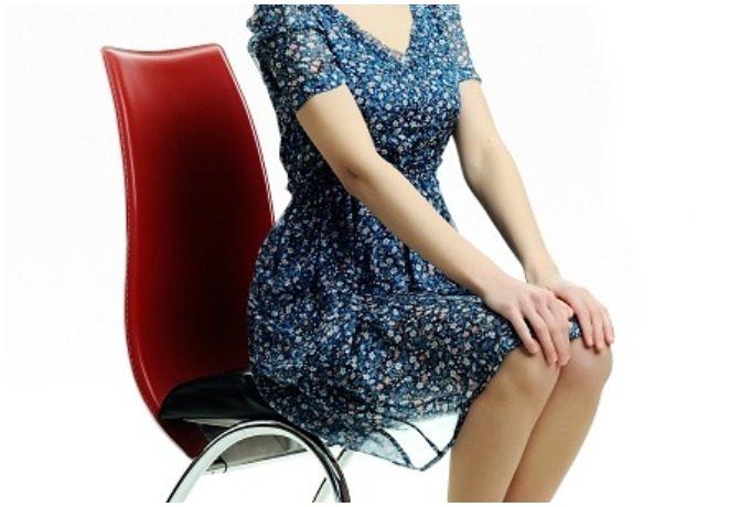 坐骨を立て姿勢良く椅子に座る女性