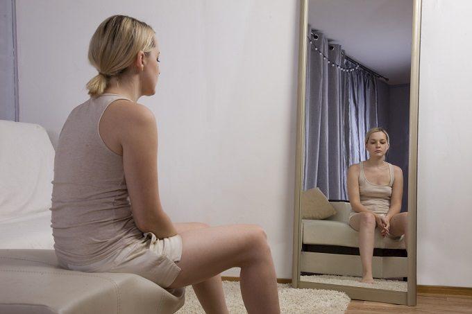 うつむいて座る女性とその姿が映る鏡