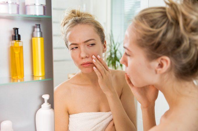 鏡の前で自分の肌を気にする女性