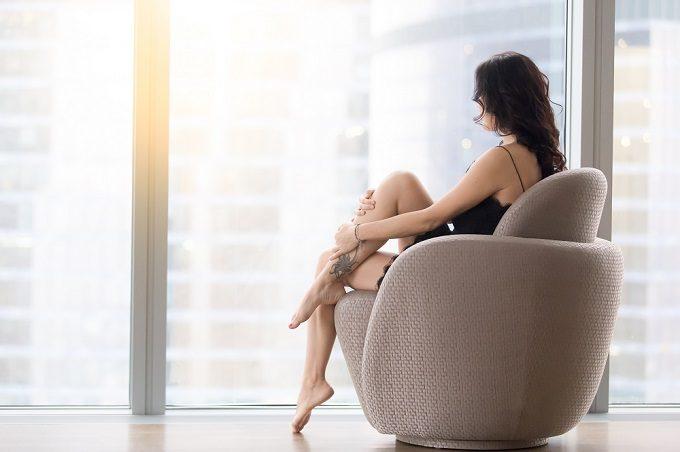椅子に座って窓の外を眺める女性