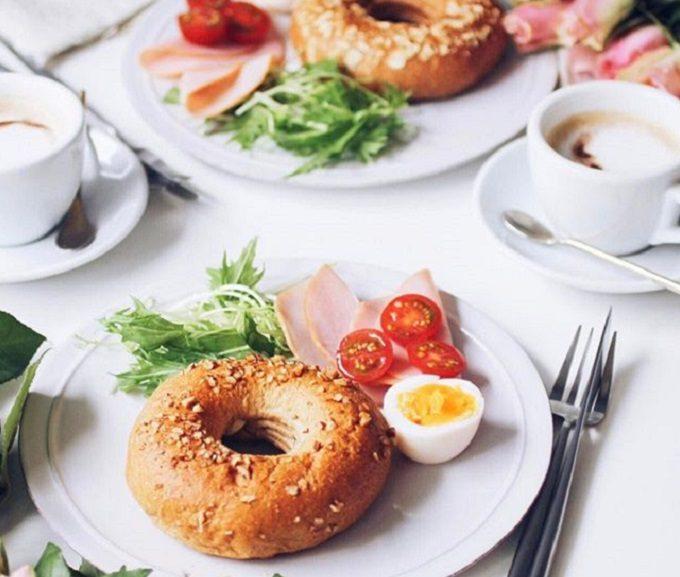ベーグルのようなリング型のふすまパンと料理が並ぶ食卓