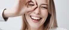 目元にOKサインをあてる笑顔の女性