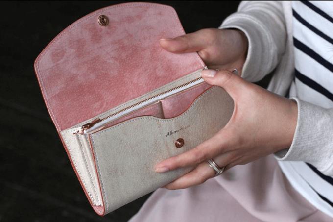 珊瑚色の長財布を持つ女性の手元