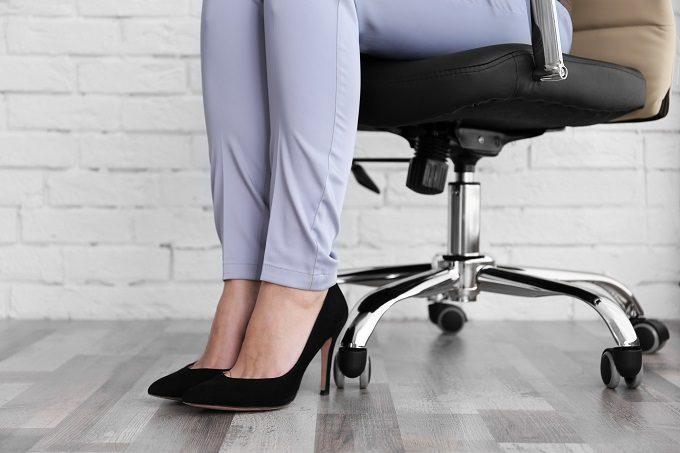 脚をとじて椅子に座る女性