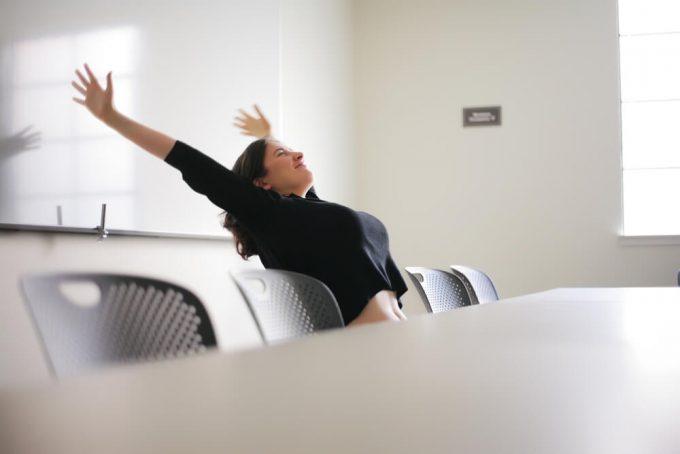 肩、肩甲骨まわりが凝って大きく伸びをする女性