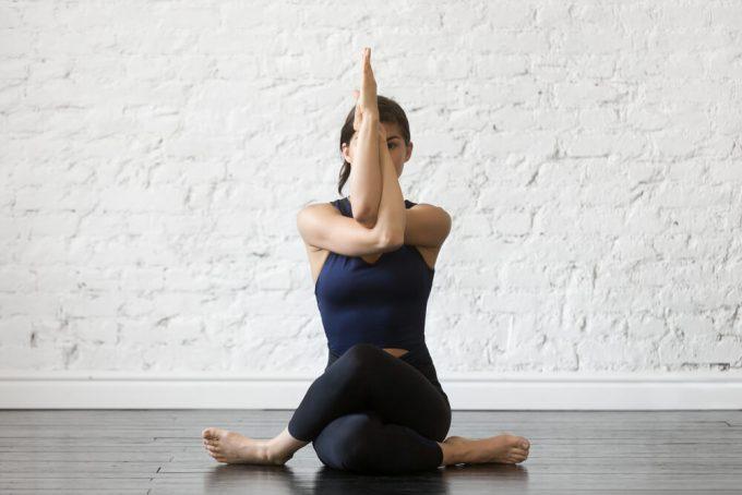 肩の後ろ側の筋肉をのばすストレッチをする女性