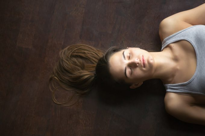 目を閉じて仰向けになっている女性