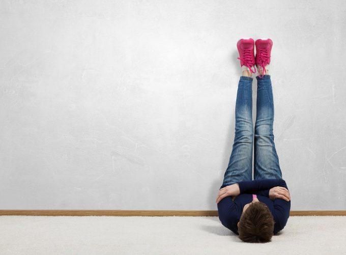 壁に両脚をあげて、股関節を柔らかくする股関節ストレッチを行う女性