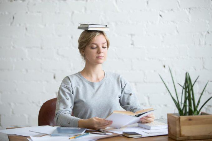 正しい姿勢をキープするために頭の上に本を乗せている女性